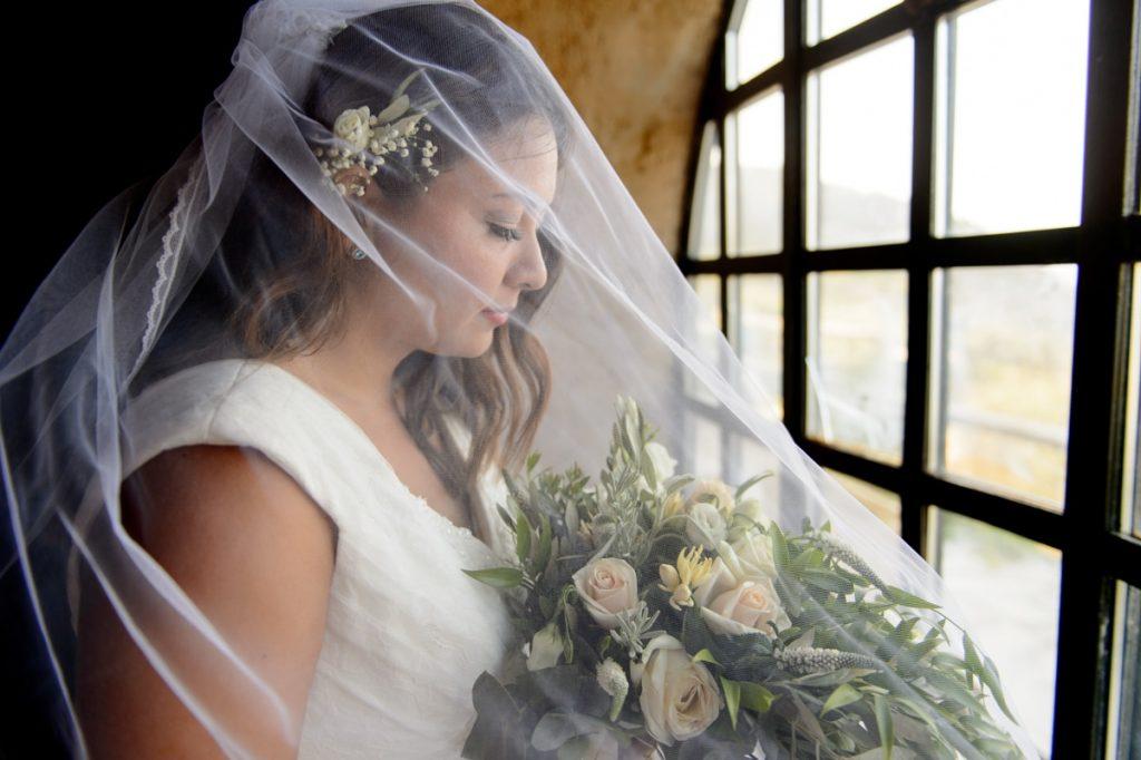 Νύφη με πέπλο και νυφική ανθοδέσμη