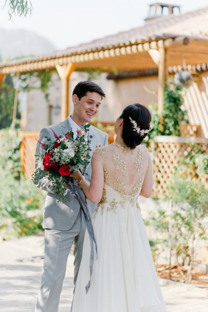 groom and bride with red wedding bouquet