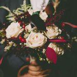 Νυφική ανθοδέσμη με λευκά τριαντάφυλλα και κόκκινες λεπτομέρειες