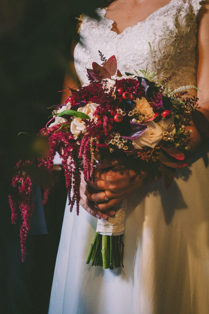 Bridal bouquet in dark red colors with cala lilies, roses and berries