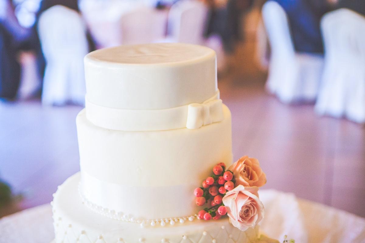 Τριόροφη λευκή τούρτα με φρέσκα λουλούδια