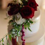 διώροφη τούρτα με χρυσές λεπτομέρειες και κόκκινα τριαντάφυλλα